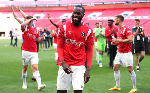 Salford City's Gus Mafuta and team-mates celebrate after winning the Vanarama National League Play-off Final at Wembley Stadium.