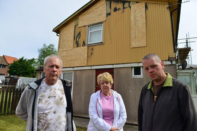 William and Fiona with their son William Holland (right) outside of their damaged home.