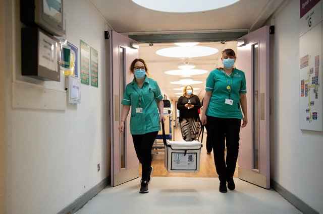 Pharmacists transport a cooler containing the Moderna vaccine, at the West Wales General Hospital in Carmarthen, the third vaccine to be approved for use in the UK, which is to be given to patients in Wales from Wednesday, April 7.