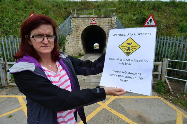 Councillor Rachel Creevy holding the Rip Tide warning poster near Steetley beach. Picture by FRANK REID