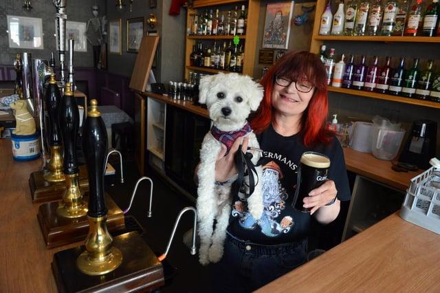 The Fishermans Arms landlady Hazel Whitelock with dog Sunny behind the bar.