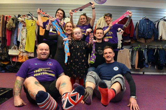 Bella Gill, six, with Micky Day and Darren Cliff (front) parents Donna Fenwick and Daniel Gill (centre) and members of the Miles for Men team.