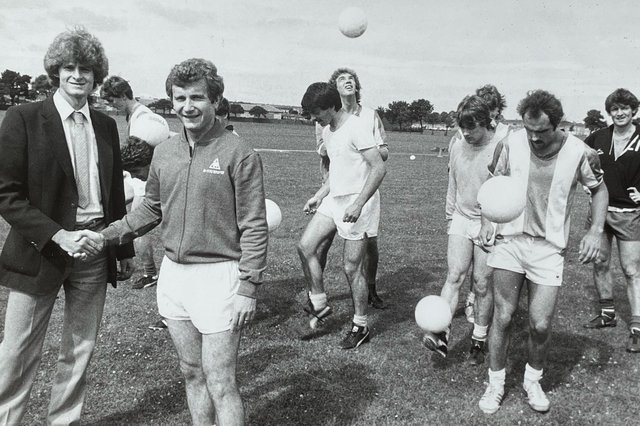 Council trainee Alastair Rae, far left, shakes Hartlepool United manager Mick Docherty's hand in 1983 after brokering a deal for the club to use council pitches for training. Also pictured are Andy Linighan, who is the further back of the two players next to Alastair, Phil Brown, who is wearing a plain T-shirt in the centre of the photo and John Bird, far right.