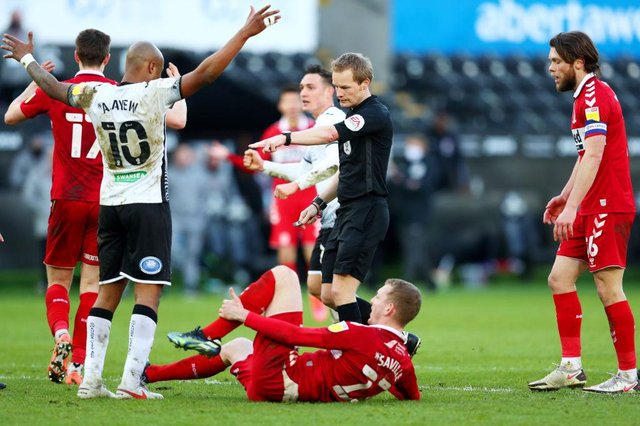 Referee Gavin Ward points to the spot as he awards a penalty to Swansea City.