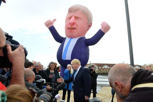 A giant inflatable of Boris Johnson stands over the PM as he visits Jackson's Wharf, Hartlepool, following the by-election victory to congratulate new MP Jill Mortimer.