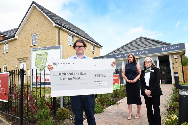 Iain Caldwell, CEO of Hartlepool and East Durham Mind, receives a cheque for £1,000 from Barratt and David Wilson's Elwick Gardens sales office staff.