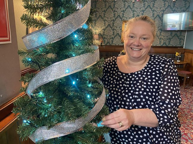 Deborah Humberston decorating a Christmas Tree in the Nursery Inn ahead of the pub's May 30 Christmas carol service.
