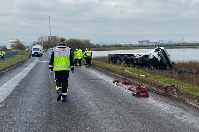 The tanker lying on its side after leaving the road