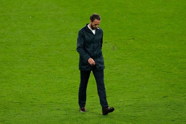 Gareth Southgate, Head Coach of England looks dejected as he walks across the pitch.