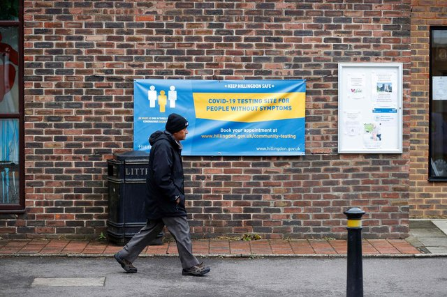 A man walks past a banner featuring a coronavirus testing site set up at St Mary's Church hall in the London borough of Hillingdon, England on May 14, 2021, as part of surge testing to monitor and suppress the spread of the Covid-19 variant first identified in India. - The Indian coronavirus variant has been detected in a number of areas in England which are reporting the highest rates of infection, data from Public Health England (PHE) suggests. (Photo by Adrian DENNIS / AFP) (Photo by ADRIAN DENNIS/AFP via Getty Images)