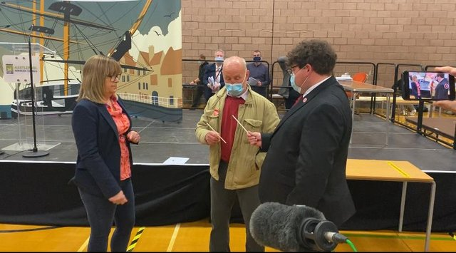 Moss Boddy, centre, draws the winning straw watched by council managing director Denise McGuckin, left, and Anthony Frain, right, who was Julie Clayton's election agent.