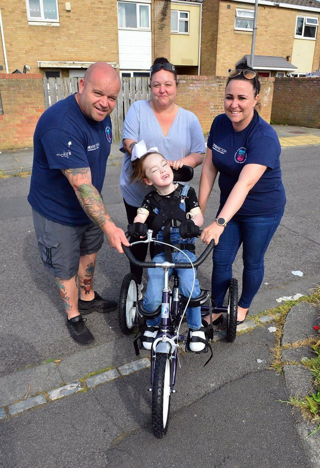 Tilly Grant on her specially adapted trike with Micky Day, Karen Willgress and Kelly Pearson from Miles for Men. Picture by FRANK REID