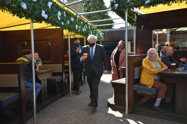 Prime Minister Boris Johnson carries a pint through a beer garden on the local election campaign trail. Picture: Jacob King - WPA Pool/Getty Images.