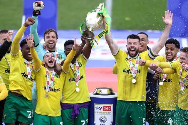 Alexander Tettey and Grant Hanley of Norwich City lift the Sky Bet Championship trophy.