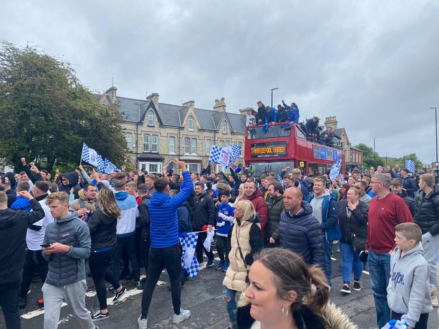Fans cheer on as the bus passes through the town.